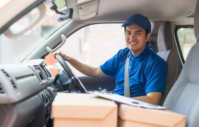 delivery man smiling while inside the car with packages